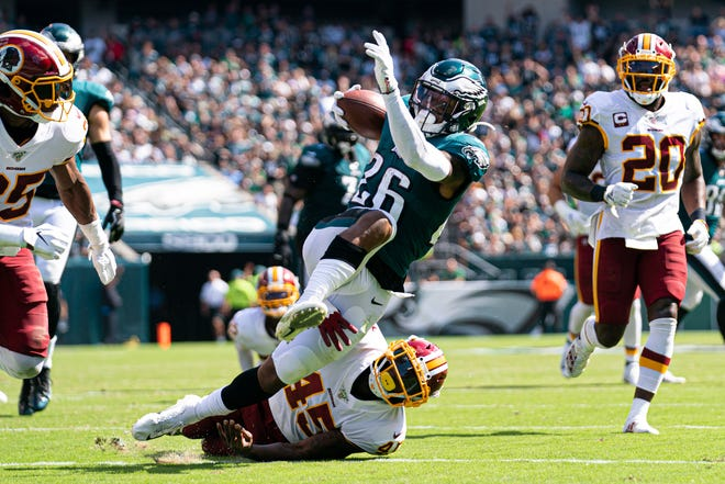 Eagles running back Miles Sanders (26) is tackled by Redskins cornerback Dominique Rodgers-Cromartie earlier this season.