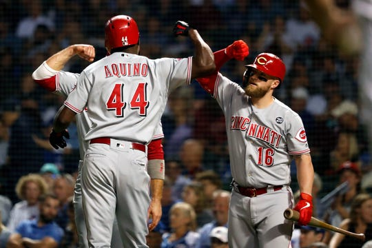 Cincinnati Reds' Aristides Aquino celebrates with Tucker Barnhart (16) and Joey Votto after hitting a two-run home run off Chicago Cubs' Yu Darvish during the first inning of a baseball game Tuesday, Sept. 17, 2019, in Chicago.