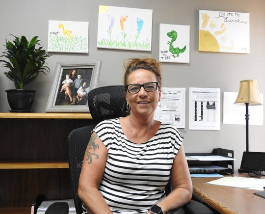 Denise Nelson in her office at Coshocton County Job and Family Services featuring photos of her family and paintings by her grandchildren. She will receive an award Sept. 27 in Columbus for being named Caseworker of the Year by the Public Children Services Association of Ohio.