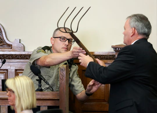 Delaware County Attorney John Bernau, right, questions witness Delaware County Deputy Eric Holub as he hands back a corn rake during the first-degree murder trial for Todd Mullis at Dubuque County Courthouse in Dubuque on Tuesday, Sept. 17, 2019. Todd Mullis is accused of killing Amy L. Mullis by stabbing her with that rake on Nov. 10.