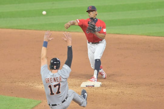 Cleveland Indians shortstop Francisco Lindor (12) turns a double play beside Detroit Tigers catcher Grayson Greiner (17) in the fifth inning at Progressive Field on Tuesday, Sept. 17, 2019, in Cleveland.