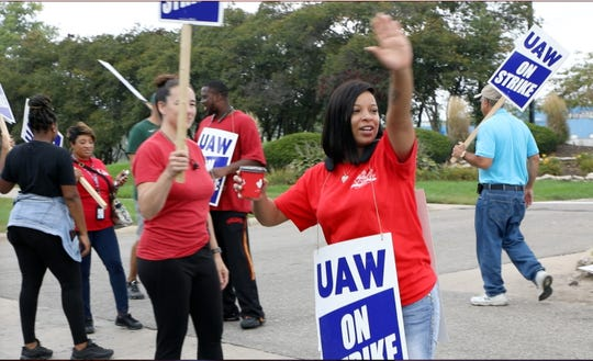 Denise Hill a GM assembly worker from Detroit waves at passing traffic to keep her spirits up on her 37th birthday as she and other UAW members picket outside Romulus Powertrain in Romulus, Mich., Tuesday, Sept. 17, 2019.  Hill has worked alongside GM employees for 3 years as a temp and still hasn't been hired in.