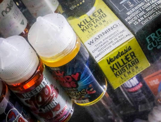 Flavored vaping solutions are shown in a window display at a vape and smoke shop, Monday Sept. 16, 2019, in New York.