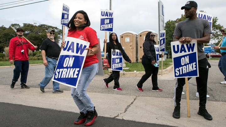 Denise Hill a GM assembly worker from Detroit, dances and waves to traffic to keep her spirits up on her 37th birthday as she and other UAW members picket outside Romulus Powertrain in Romulus, Mich., Tuesday, Sept. 17, 2019. Hill has worked alongside GM employees for 3 years as a temp and still hasn't been hired in.