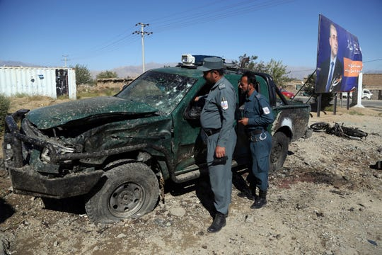 Afghan police inspect the site of a suicide attack, in northern Parwan province, Afghanistan, Tuesday, Sept. 17, 2019. The Taliban suicide bomber on a motorcycle targeted presidential guards who were protecting President Ashraf Ghani at a campaign rally in northern Afghanistan on Tuesday, killing over 20 people and wounding over 30. Ghani was present at the venue but was unharmed, according to his campaign chief.