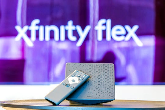 In this Monday, Sept. 16, 2019 photo, an Xfinity Flex device is displayed in Philadelphia. As big entertainment companies prepare to launch their new streaming services, Comcast is trying to bolster Flex, its Roku-like streaming bundle, by dropping its $5 fee.