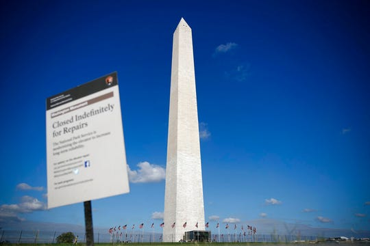 The Washington Monument is seen past a sign greeting visitors during a press preview tour ahead of the monument's official reopening, Wednesday, Sept. 18, 2019, in Washington. The monument, which has been closed to the public since August 2016, is scheduled to re-open Thursday, Sept. 19.