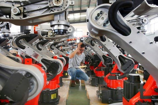 In this Wednesday, Sept. 11, 2019, photo, a man checks on the robotic arms at a factory making industrial robots in Zhengyu town of Haimen city in east China's Jiangsu province.