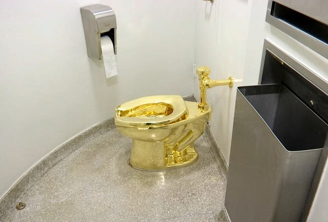 """FILE - This Sept. 16, 2016 file image made from a video shows the 18-karat toilet, titled """"America,"""" by Maurizio Cattelan in the restroom of the Solomon R. Guggenheim Museum in New York. Thieves have stolen the solid gold toilet worth up to 1 million pounds from Blenheim Palace, the birthplace of Winston Churchill."""
