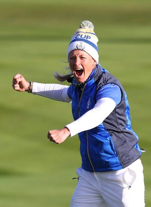 Suzann Pettersen celebrates after holing a putt on the 18th green to win the Solheim cup against the U.S.