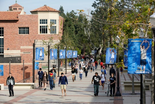 FILE - In this Feb. 26, 2015, file photo, students walk on the University of California, Los Angeles campus. Xiaoning Sui, 48, of Surrey, British Columbia, is accused of paying $400,000 to get her son into the University of California, Los Angeles, as a fake soccer recruit. She has become the 52nd person charged in a sweeping college admissions bribery scheme, according to an indictment unsealed Tuesday, Sept. 17, 2019, in Boston's federal court.