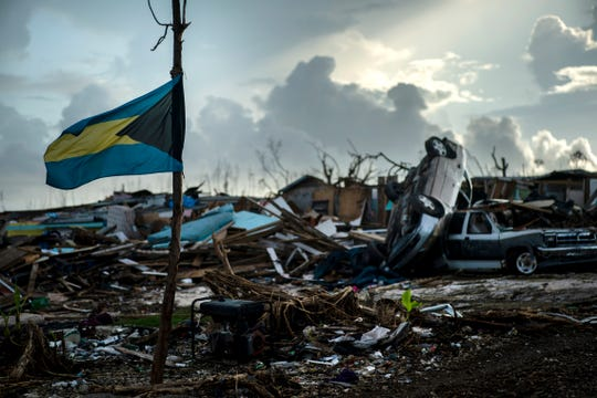 A Bahamas flag flies tied to a sapling, amidst the rubble left by Hurricane Dorian in Abaco, Bahamas, Monday, Sept. 16, 2019. Dorian hit the northern Bahamas on Sept. 1, with sustained winds of 185 mph (295 kph), unleashing flooding that reached up to 25 feet (8 meters) in some areas.