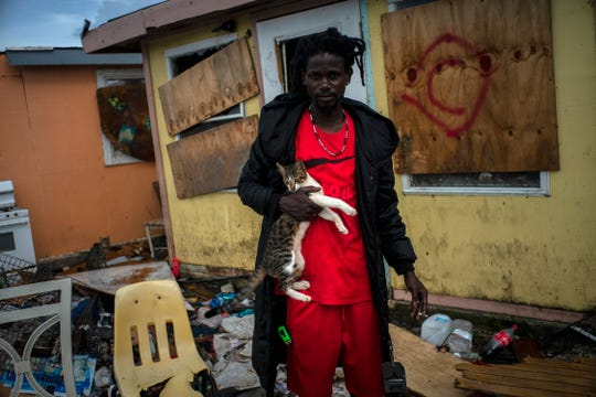 Vladimir Safford, an immigrant from Haiti, poses with his cat next the rubble of his home, in the aftermath of Hurricane Dorian in Abaco, Bahamas, Monday, Sept. 16, 2019.