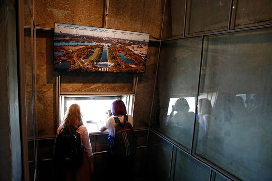 Visitors look out from the observation level inside the Washington Monument during a press preview tour ahead of the monument's official reopening, Wednesday, Sept. 18, 2019, in Washington.
