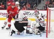The Red Wings' Michael Rasmussen puts a shot on goal that hits the knee of the Blackhawks' Carl Dahlstrom and goes into the net past goalie Kevin Lankinen for the go-ahead goal late in the third period.
