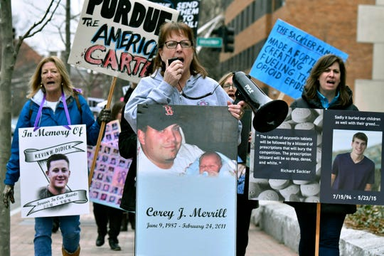 In this Friday, April 12, 2019 file photo, Cheryl Juaire, of Marlborough, Mass., center, leads a protest near the Arthur M. Sackler Museum at Harvard University, in Cambridge, Mass.