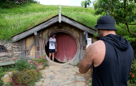 In this Dec. 31, 2015, file photo, tourists take photos during a tour of the Hobbit movie set near Matamata, New Zealand.
