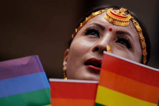 In this Aug. 16, 2019, photo, a participant holds a rainbow flag before marching in a gay pride parade in Kathmandu, Nepal.