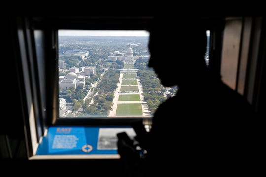 A visitor looks out toward the U.S. Capitol from the Washington Monument's observation level Wednesday, Sept. 18, 2019.