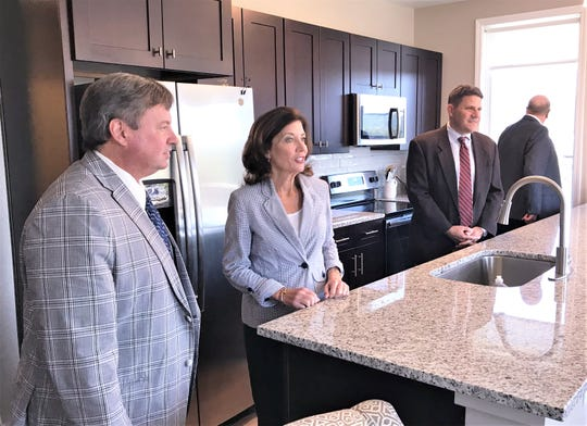 Elmira Mayor Dan Mandell, left, Lt. Gov. Kathy Hochul and others get a tour of upscale apartments in the new mixed use building at 100 W. Water St. in Elmira on Wednesday.
