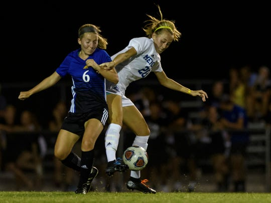 Castle's Skylar Day (6) and Memorial's Ryleigh Anslinger (20) fight for possession of the ball at Castle Soccer Stadium in Newburgh, Ind., Tuesday night, Sept. 17, 2019. Following two overtime periods and a 6-5 penalty kick battle, the Castle Knights defeated the Memorial Tigers, 3-2.