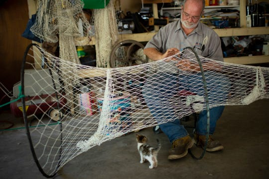 Master net maker Larry Haycraft of Petersburg, Ind., attaches a hoop to a knotted hoop net in his workshop in August of 2019 under the watchful eyes of Catfish, a neighbor's kitten.