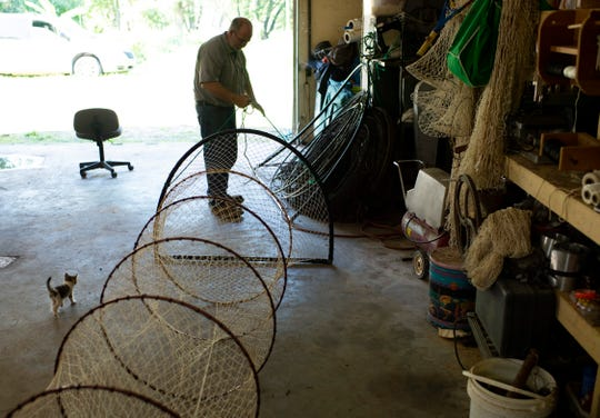 "Master net maker Larry Haycraft of Petersburg, Ind., is confronted by Catfish, the neighbor's kitten, as he stretches a knotted hoop net in his workshop in August of 2019. One of Haycraft's customized options for his nets is a ""square-D"" opening for certain river situations."