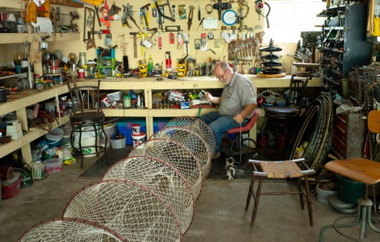 Master net maker Larry Haycraft of Petersburg, Ind., is confronted by Catfish, the neighbor's kitten, as he tries to finish off a knotted hoop net in his workshop in August of 2019.