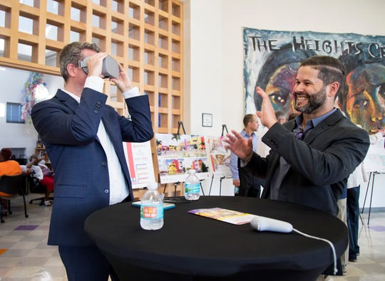 Jan-Erik Hustrulid, left, looks at a virtual reality rendering of the new building for the Harlem Heights Community Charter School and GLAD early learning center on Wednesday, Sept. 18, 2019, following the groundbreaking ceremony.
