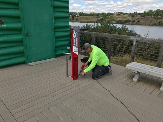 Steffen Janiula, trails coordinator for Great Falls Park and Recreation, installs a new bike repair station at the Caboose trailhead.