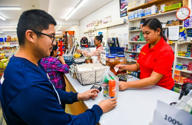 Dededo resident Edmund Valencia purchases the last three aerosol cans of insect repellant at the La Familia retail store in the along Y-Sengsong Road on Wednesday, Sept. 18, 2019.