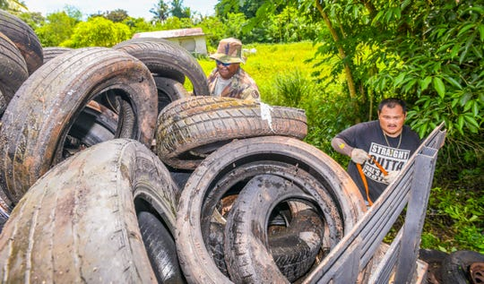 In this Sept. 18 file photo, Dededo Mayor's Office maintenance workers John Ngiraibuuch, left, and Jeric Tomagan secure a load of old tires for disposal from the Swamp Road area.