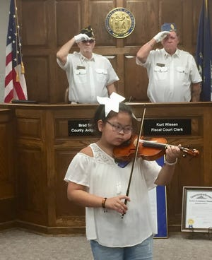"""Abigail White plays the """"Star-Spangled Banner"""" while members of the American Legion Worsham Post No. 40 Honor Guard salute."""