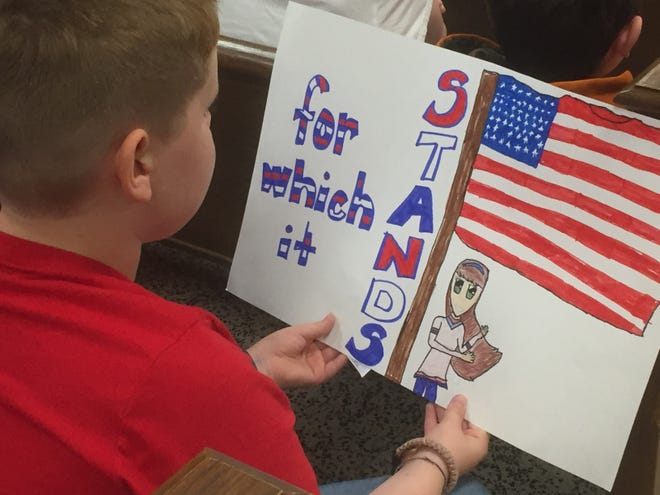 Bend Gate Elementary fifth-grader Cole Gish looks at his sign while taking part in Wednesday's Constitution Day program, put on by the General Samuel Hopkins Chapter of the DAR, takes place Wednesday in the courthouse.