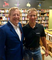 Carmel Mayor Jim Brainard (from left) and Dave Schweikert, pose together during roundabout trivia at Books & Brews Carmel in celebration of National Roundabout Week 2019.