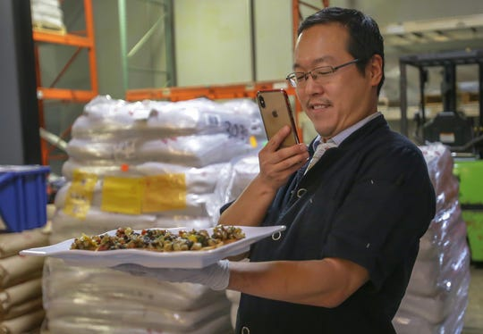 Executive Director of Brooklyn Bugs and owner of Yummy Eats Joseph Yoon takes a photo of one of his dishes with bugs, Wednesday, Sept. 18, 2019, at SunKing Brewery, Indianapolis. Yoon is based out of Brooklyn, NY and makes dishes with edible insects such as mule worms, crickets and termites.