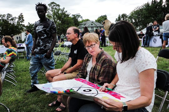 IHRC Outreach Specialist Chris Brown stands by as doctors Alison Lynch and Andrea Weber sign a poster Saturday, Aug. 31, 2019, at the Iowa Harm Reduction Coalition in Cedar Rapids, Iowa.