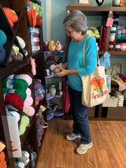 Mary Hudson of Starkville studies the yarn at The Southern Needle in Ridgeland.