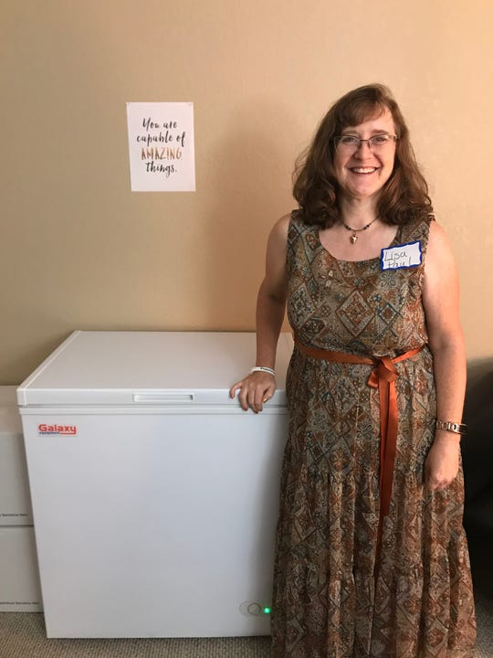 Lactation consultant Lisa Paul stands next to a freezer in her office that will be used to store donated breastmilk overnight before it's shipped to a processing facility in Texas.