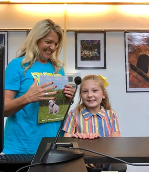 """Martial F. Billeaud Elementary Principal Christy Hayes recognizes fourth-grader Anna Luneau at the Sept. 11 Lafayette Parish School Board meeting as the winner of a school competition to choose the new school's mascot. She proposed a bulldog named """"Suga"""" or Sugar."""