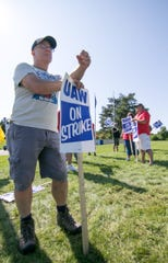 Pete Ogg, a durability test car driver team lead at the GM's Milford Proving Grounds, pickets with UAW coworkers Wednesday, Sept. 18, 2019 at the entrance on Hickory Ridge Road in Milford Township.