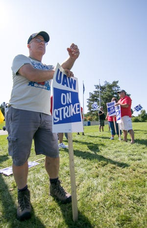 Pete Ogg, a durability test car driver team lead at the GM'sMilfordProving Grounds, pickets with UAW coworkers Wednesday, Sept. 18, 2019 at the entrance on Hickory Ridge Road in Milford Township.