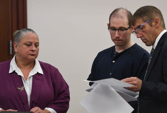 Flanked by his attorneys Timothy Williams, right, and Ina O'Briant, Michael Phinn, 33, enters Circuit Judge Clinton Canady's courtroom to be sentenced on second-degree criminal sexual conduct, assault with the intent to commit sexual contact, unauthorized access to a computer, and using a computer to commit a crime.