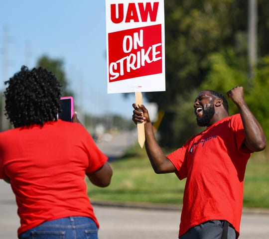 Jacquline Brent takes a picture of fellow UAW member Porter Williams, Wednesday afternoon, Sept. 18, 2019, while picketing near the GM Lansing Delta Township plant on the third day of the nationwide strike against General Motors.  Brent has worked at GM for 31 years, and Williams for three.