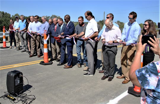 State and local officials and others involved in the Ohio 309 overpass project cut a ribbon to dedicate the new roadway on Wednesday.