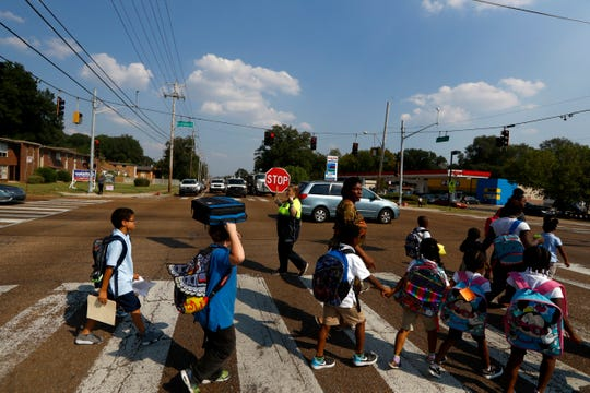 A crossing guard helps children across Summer Avenue near Grahamwood Elementary School where last week, a fellow crossing guard was struck by a car while she was working on Graham Street and Faxon Avenue.