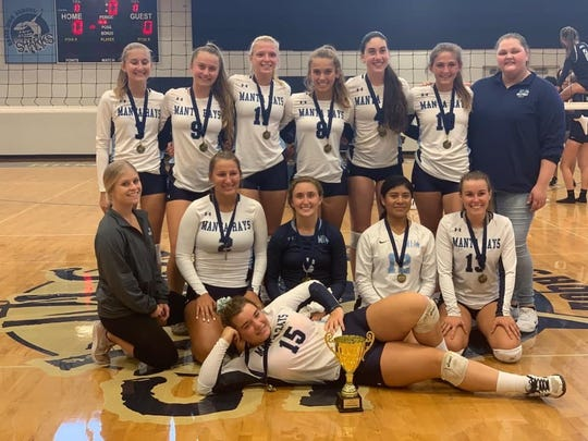 The Marco Island Academy volleyball team poses with the trophy after winning the Oasis tournament Saturday, Sept. 14. The Manta Rays have already surpassed last season's win total, establishing a school record for wins in a season.