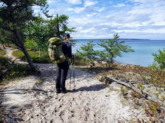 Courtney Lamm looks out over Lake Superior, with Grand Island in the distance, while hiking on the North Country Trail near Miners Beach in Pictured Rocks National Lakeshore on Sept. 15, 2019.