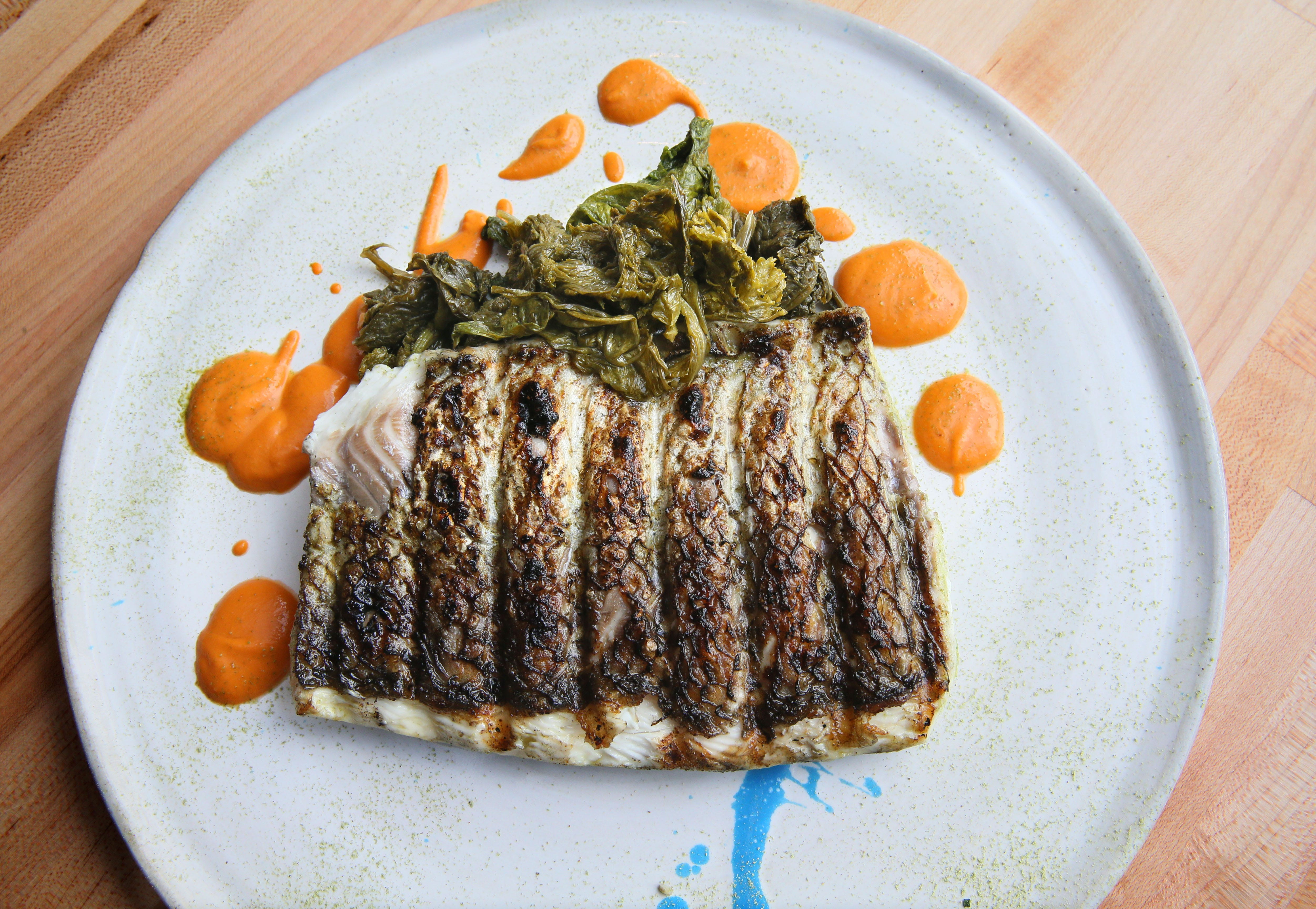 Birch + Butcher serves its grilled whitefish with tomato butter and kicky fermented mustard greens.