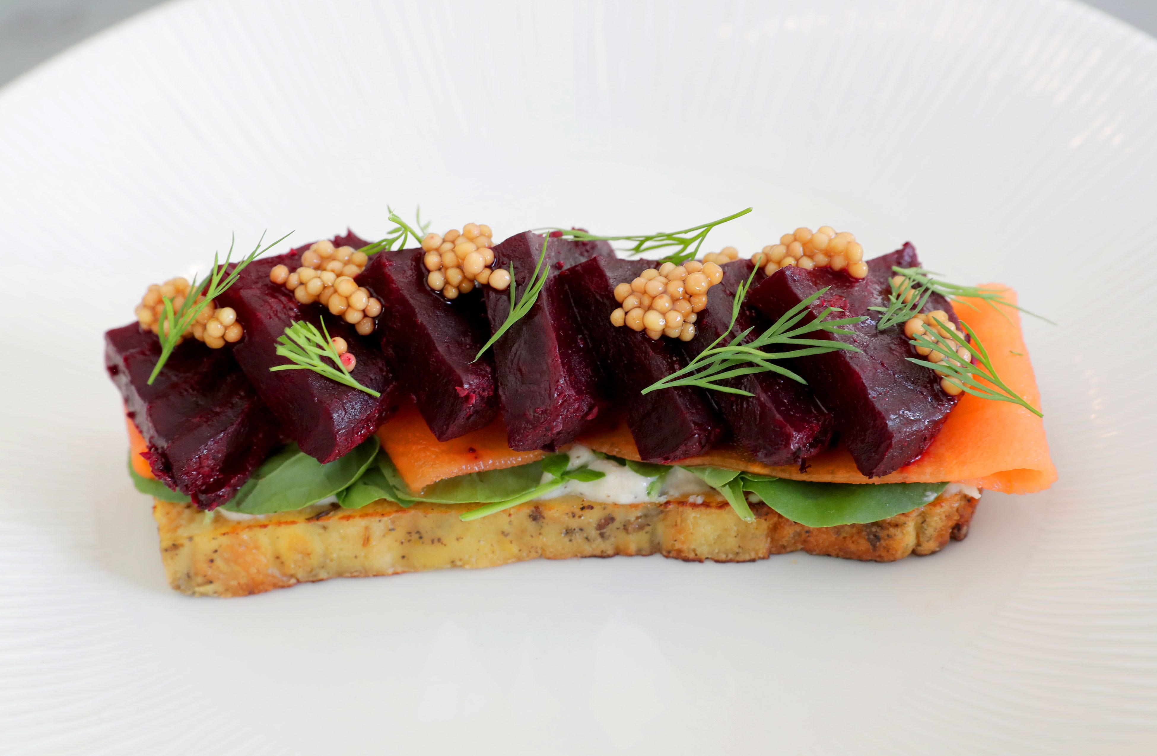 Beets seasoned to taste like pastrami are placed over pain perdu — French toast — with spiced pickled mustard seeds, watercress, horseradish creme fraiche, and pickled carrots for an appetizer at Buckley's Restaurant.